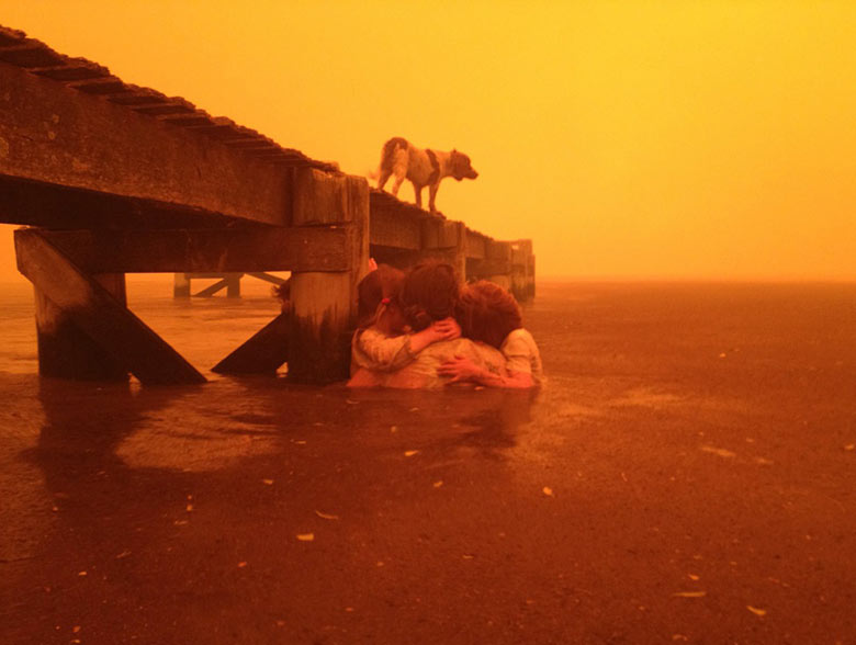 Tammy Holmes and her grandchildren take refuge under a jetty as a wildfire rages, Australia